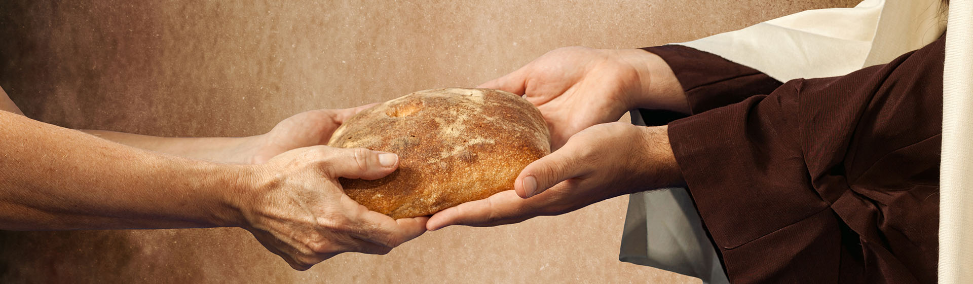 rustic photo depicting Jesus' hands handing a loaf of bread to another man